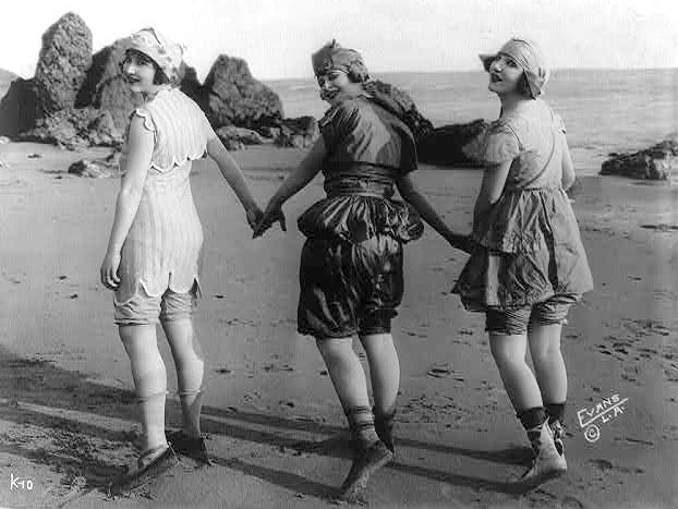 Three bathing beauties with hands joined, wearing vintage bathing suits on beach, c.1918.