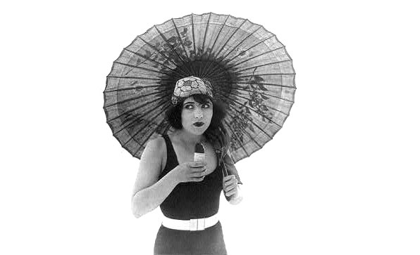 1920s movie star standing with umbrella in bathing suit eating Eskimo Pie.