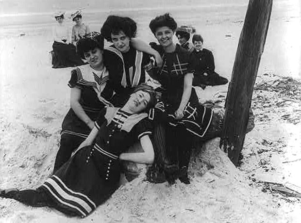 Photograph from 1906 shows four young women wearing vintage bathing suits sitting on sand at the beach.