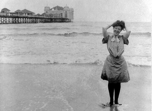 Happy and beautiful bather posing in front of Atlantic City boardwalk in 1903.