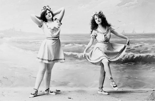 Two girls wearing vintage bathing clothing, posed in front of beach backdrop in 1902.