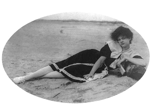Woman in vintage bathing suit lying on beach, c.1910.