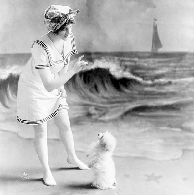 Young woman in vintage bathing suit in front of studio backdrop of beach in 1913.