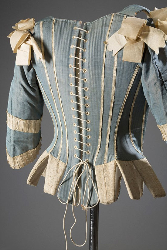 Sleeved corset (then called stays), circa 1770, made from sky-blue silk with decorative ivory ribbons that crisscross over the stomach. Stiffened with whalebone, possibly Europe. Deeper meaning: Buried within the beauty of this intricate Rococo-era corset is a socioeconomic message. Due to the artifact's constrictive nature and French court hue, its wearer likely led a life of work-free leisure. [Image credit: Fashion Institute of Technology, www.fitnyc.edu/museum.asp]