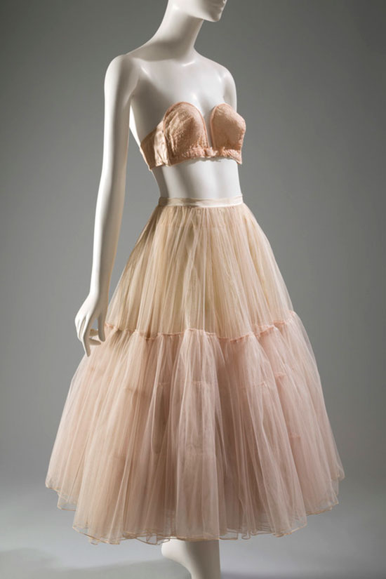 A 1951 Christian Dior petticoat (nylon net, taffeta, and horsehair net ) and a 1949 Poirette nylon lace bra exemplify the mid-20th century feminine form. [Image credit: Fashion Institute of Technology, www.fitnyc.edu/museum.asp]