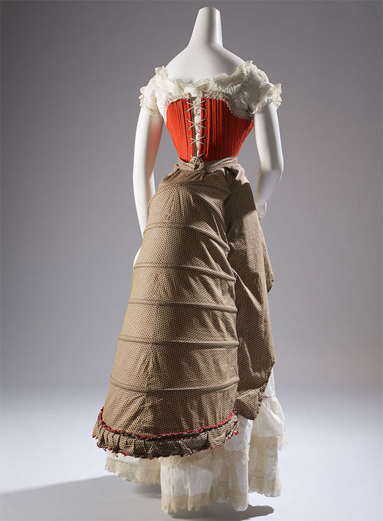 Victorian era corset of wool, silk, cotton and steel, circa 1880. The rise of steel in the industrial 19th century led to innovations in fashion as well, including this underskirt and corset - used to cut the era's infamous S-curve silhouette - which utilized metal instead of whalebone to achieve its structure. [Image credit: Fashion Institute of Technology, www.fitnyc.edu/museum.asp]