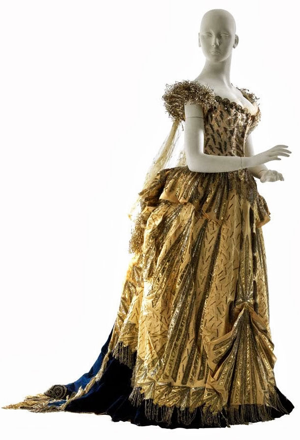 "WORTH FANCY DRESS, C.1883 Fancy dress costume by Maison Worth representing ""Electric Light,"" 1883 • Worn by Mrs. Cornelius Vanderbilt II to the Vanderbilt Ball. Designed by Charles Frederick Worth, the most famous Parisian couturier of the day, and made of satin, velvet, and silver bullion, Mrs. Vanderbilt's costume was meant to represent ""Electric Light,"" in honor of Thomas Edison's new power station in New York. Museum of the City of New York, Gift of Countess Laszlo Szechenyi, 51.284.3"