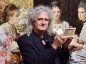 Brian May in front of John Everett Millais's Hearts are Trumps, which was inspired by Michael Burr stereoscopic photograph.  [Photograph: Ben Stansall/AFP]