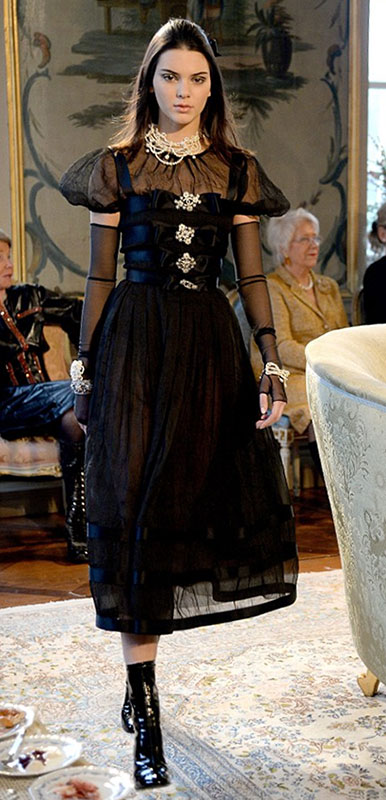 Young model, Kendall Jenner, travels back in time in a sheer black Chanel Karl Lagerfeld dress with Victorian style accessories.